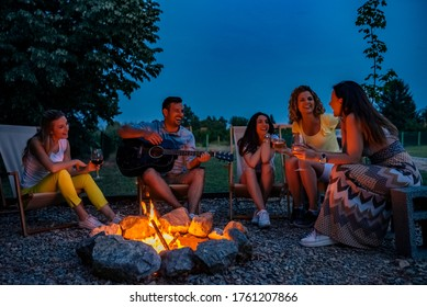 Friends laughing, singing and playing guitar around the firepit outdoors.