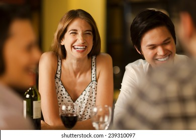 Friends laughing together in a restaurant at night