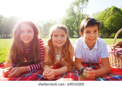 Friends laying on the picnic blanket at sunny day