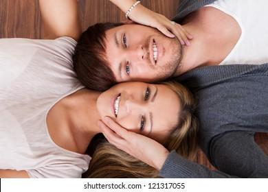Friends lie alongside opposite heads on wooden floor.