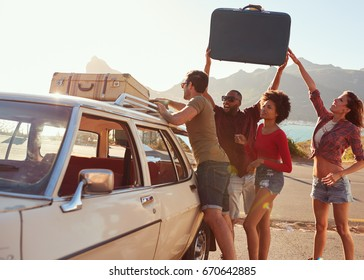 Friends Loading Luggage Onto Car Roof Rack Ready For Road Trip