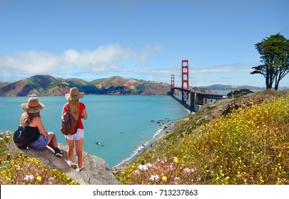 Friends  looking at beautiful summer coastal landscape, on hiking trip.Girls sitting, relaxing on mountain.Golden Gate Bridge, over Pacific Ocean and San Francisco Bay , San Francisco, California, USA