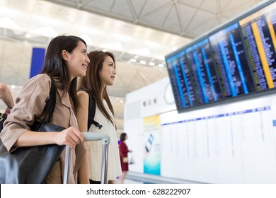 Friends looking on the flight number in international airport