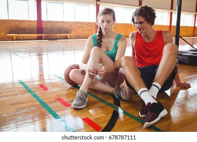 Friends looking at smart phone while sitting on harwood floor in basketball court