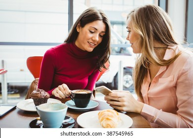 Friends looking at smartphone in cafe