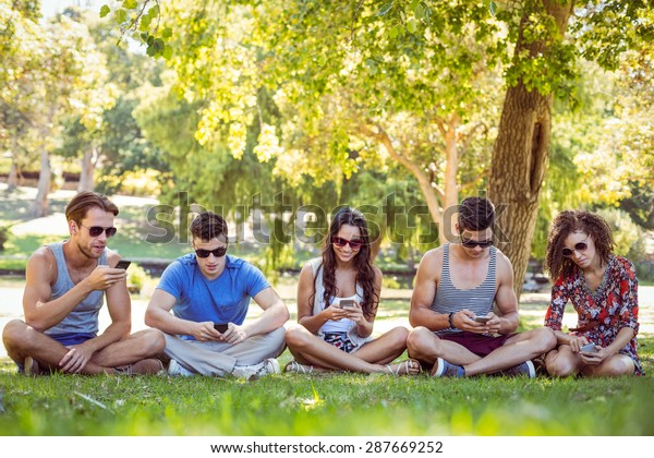 Friends looking at their smartphone in the park on a sunny day