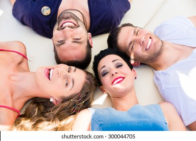 Friends lying in sand on beach, two women and two men