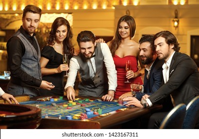 Friends make bets gambiling at the roulette table in the casino.