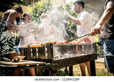 Friends making barbecue in the garden