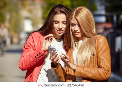 Friends making selfie. Two beautiful young women making selfie and grimacing