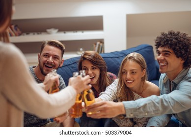 Friends making a toast with beer at home.