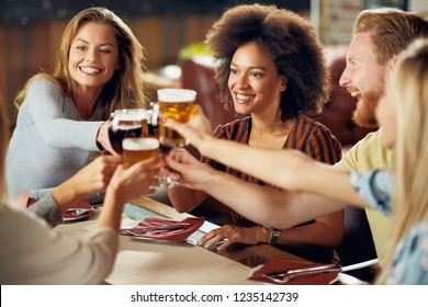 Friends making a toast while sitting in restaurant. Multi-ethnic group.