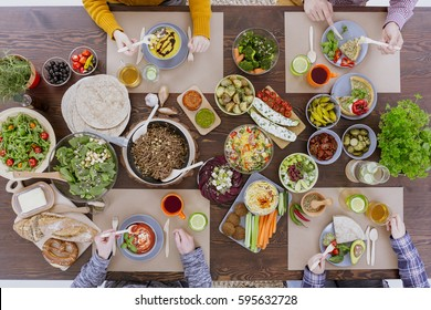 Friends meeting by the table full of vegetarian food