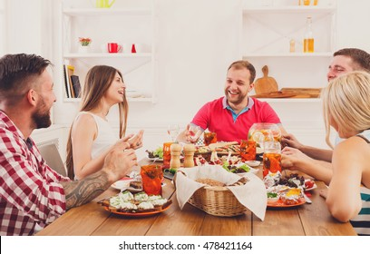 Friends meeting. Group of happy people with glasses, talking, eating healthy meals at party dinner table in cafe, restaurant. Young company celebrate with alcohol and food at wooden table indoors.