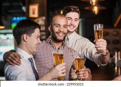Friends met after a hard day. Three cheerful friend clink beer at the bar and drink a beer while the bartender is standing on the bar. Friends having fun together