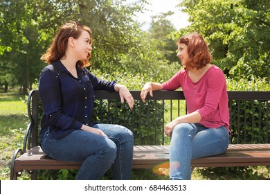 Friends met in the park. Girls talking while sitting on a bench