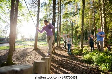 Friends Motivating Woman Crossing Log Bridge In Forest