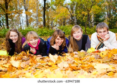 Friends on autumn leaves, laughing