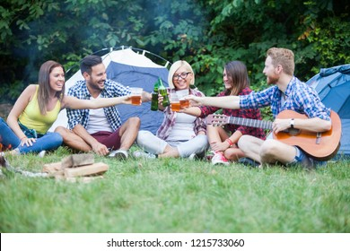 Friends on camping making toast with beer