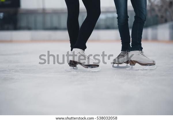 Friends on skates at ice-skating rink.