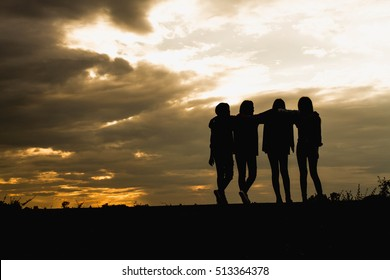 Friends on the sunset. Silhouette of group in sunset .