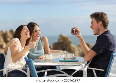 Friends on vacations laughing and taking photo with a smart phone in a restaurant on the beach