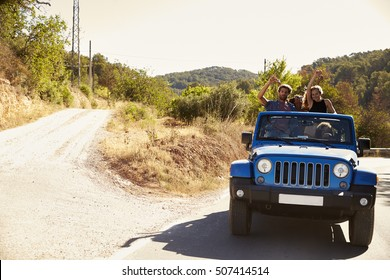 Friends in an open car, passengers standing in the back