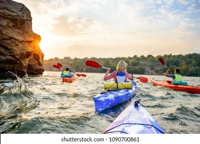 Friends Paddling Kayaks on the Beautiful River or Lake near High Rock under the Dramatic Evening Sky at Sunset. Travel and Adventure Concept.