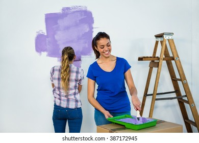 Friends painting a wall in new house