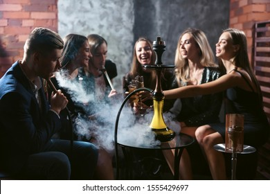 Friends party in hookah lounge. Group of people women and men smoking shisha in cafe or bar, having fun, smiling. Relax concept. Friendship