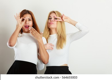 Friends people fashion concept. Two crazy girls playing around together. Young ladies have white blouse dark skirt. Women posing in funky way.