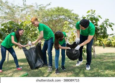 Friends picking up litter in city garden