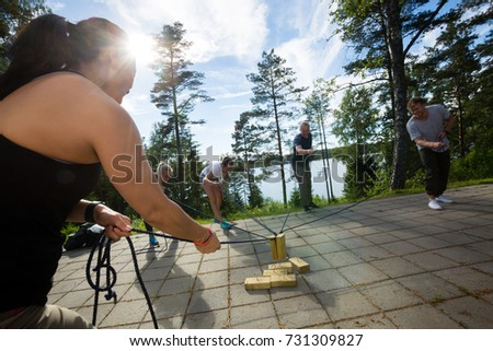 Friends Picking Up Wooden Blocks With Ropes On Patio