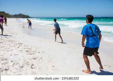 Friends play beach cricket on a hot summers day