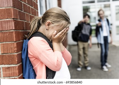 A Friends at a playground bullying about other girl in foreground