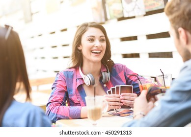 Friends playing card game while sitting at outdoor cafe