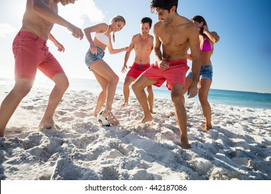 Friends playing football at the beach