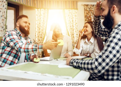 Friends playing game sticker notes to forehead. Company of friends meeting in restaurantant. Happy smiling people working online while using notebook. Freelance work, business people concept