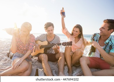 Friends playing the guitar on the beach