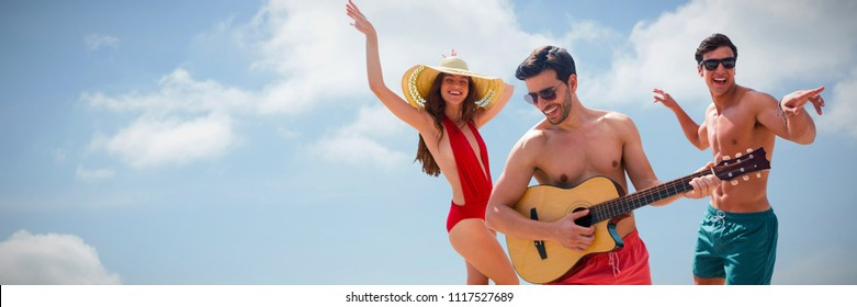 Friends playing music in swimwear against cloudy sky