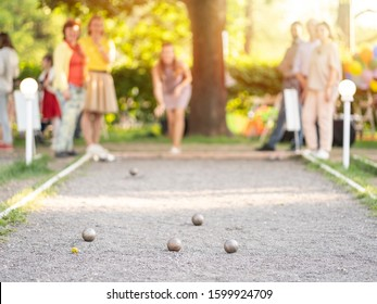Friends playing petanque woman throwing a ball outdoor city park