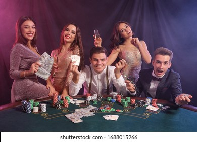 Friends playing poker at casino, at table with stacks of chips, money, cards on it. Celebrating win, smiling. Black, smoke background. Close-up.