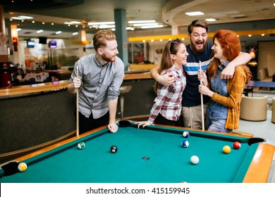 Friends playing snooker and bonding with their partner