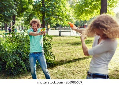 Friends playing with water pistols in the park