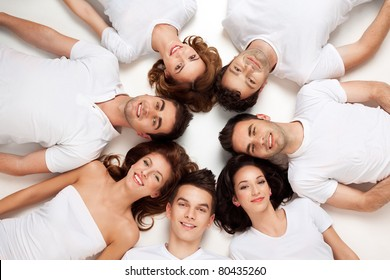 friends posing laying down on the floor looking at camera