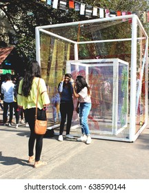 Friends posing for a photograph at the backdrop of the installation, 'The Cube of Hope', at the Kala Ghoda Arts Festival 2017 in Mumbai , India.