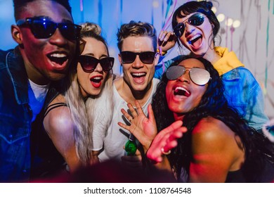 Friends posing for a selfie wearing dark sunglasses at a house party. Young men and women having fun at a colorful house party.