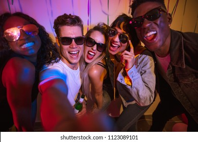 Friends posing for a selfie wearing dark sunglasses and making faces at a house party. Young men and women having fun at a colorful house party.