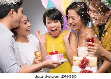 Friends presenting a birthday cake to the astonished girl