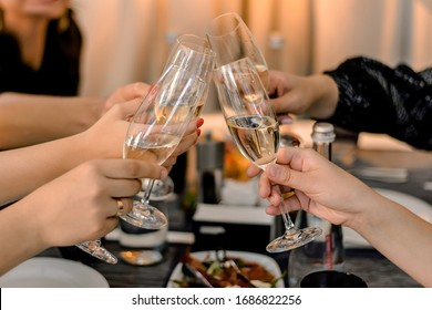 Friends raise their glasses for a toast. Hands holding glasses of champagne